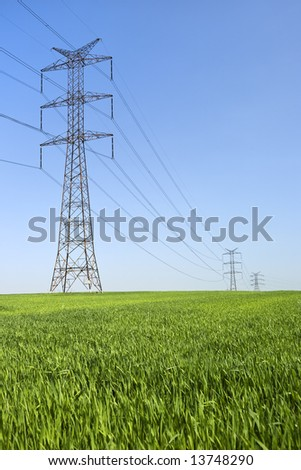 High voltage line with electricity pylons surrounded by cultivated fields