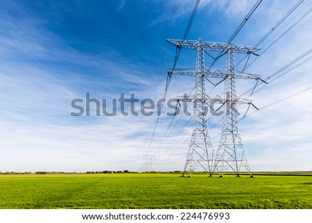 High voltage lines and power pylons in a flat and green agricultural landscape on a sunny day with cirrus clouds in the blue sky.