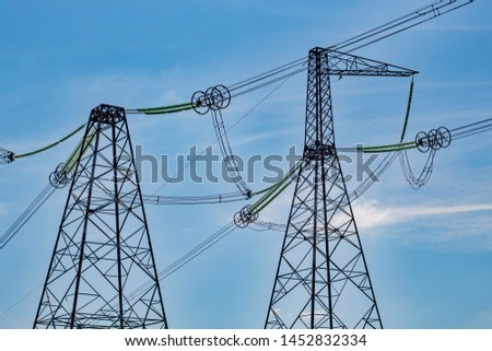 High voltage lines and reliance on a background of blue sky with clouds. Sunny day.