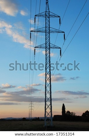 High voltage pole in front and line in diminishing perspective during evening.