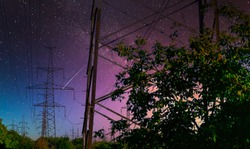 high voltage pole with Milky way on sky. high voltage power line. green energy concept of high voltage lines. high-voltage pylon