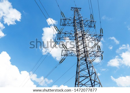High voltage poles with electrical wires. A metal pole with powerful electricity. The sky is blue with white clouds.