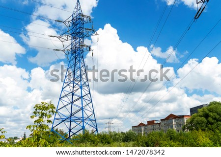 High voltage poles with electrical wires. Blue metal pole with electricity in green grass. Sky with white clouds.