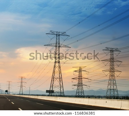 high voltage post.High-voltage tower sky background,besides the highway