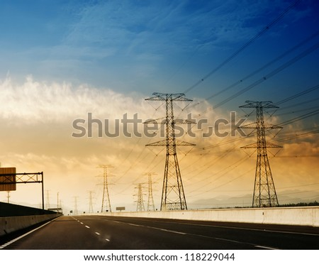 high voltage post.High-voltage tower sky background,besides the highway.