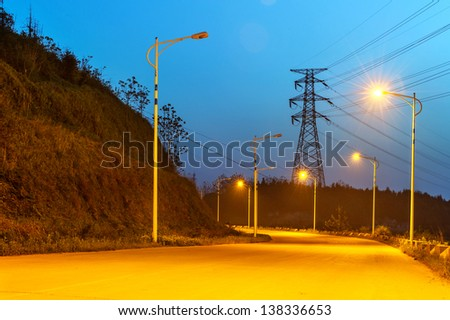 high voltage post.High-voltage tower sky background,besides the raod.