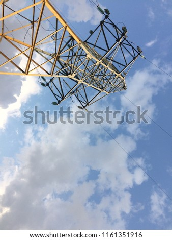 High voltage post or High voltage tower.Photo of an iron pillar, a blue sky. Industry, power network, metal tower. Cool background, bright saturated colors . #1161351916