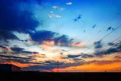 High voltage post . The power transmission towers of sunset sky background .