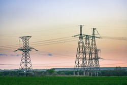 High voltage power line on industrial electricity line tower for electrification rural countryside. Energy transmisson with overhead power line