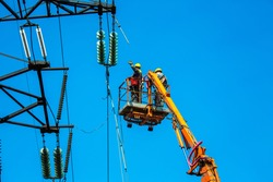 High voltage power line transmission tower workers with crane and blue sky. Hydro linemen on boom lifts working on high voltage power line towers.