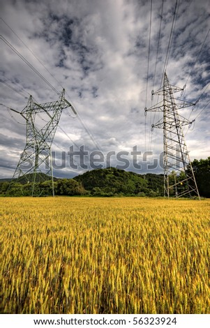 High voltage power lines above wheat field just before storm