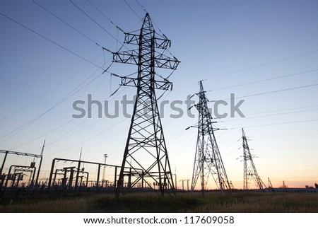 High voltage power lines at twilight at the horizon