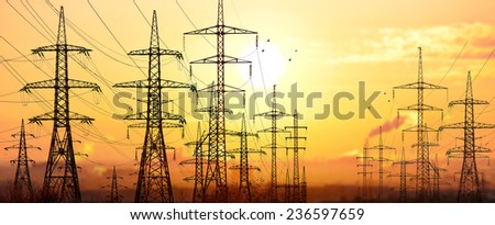 High-voltage power lines in an industrial area .On background sunrise.