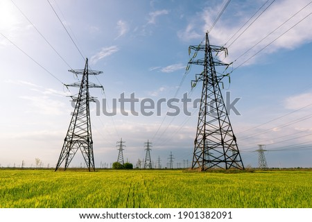 High voltage power lines leading through a green field. Transmission of electricity by means of supports through agricultural areas. Photo stock ©