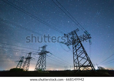 High-voltage power lines on the background of the starry sky. Four electricity pylon of high voltage lines. Silhouette of power lines on the background of beautiful starry sky. Electrical Power Grid. #668149942