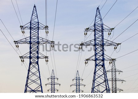 High voltage power lines pylons and electrical cables on a clear blue sky background. Modern infrastructure of high voltage transmission lines. Overhead power lines towers equipment. Energy industry. Foto stock ©