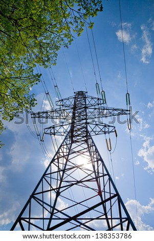 high voltage power lines with blue sky, sun and tree