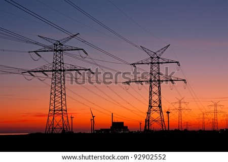 High voltage power lines with electricity pylons at twilight. At the horizon a nuclear power plant and wind turbines.