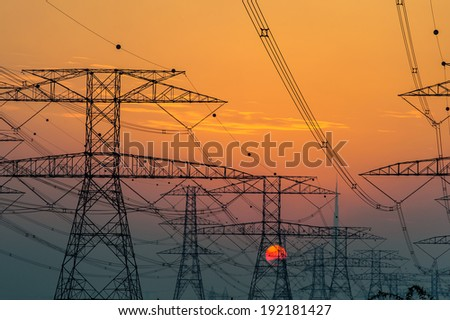 High voltage power lines with electricity pylons at twilight. At the horizon of sunset sky in Dubai desert.
