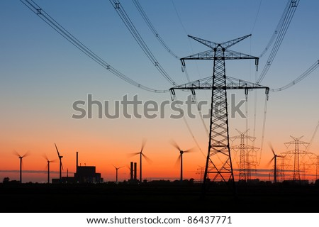 High voltage power lines with electricity pylons at twilight. At the horizon wind turbines and a nuclear power plant.