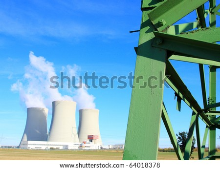 High voltage power tower close up and nuclear power plant Temelin in Czech Republic Europe Close up with shallow DOF. - stock photo
