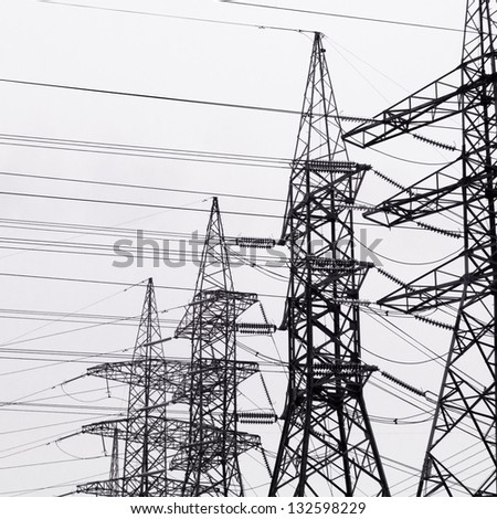 High-voltage power transmission towers in clear blue sky background.