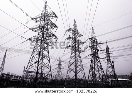 High-voltage power transmission towers in polluted gray sky background.