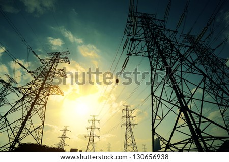 High-voltage power transmission towers in sunset sky background