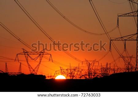 high voltage steel transmission tower during sunset