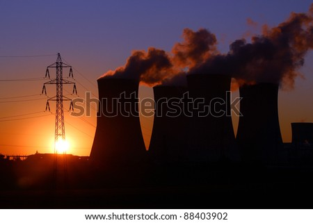 high voltage tower and power plant chimney during sunset