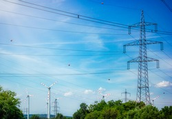 High voltage tower and wind turbine construction, beautiful landscape, blue sky, clean renewable green energy for sustainable development to prevent climate change and global warming to protect earth