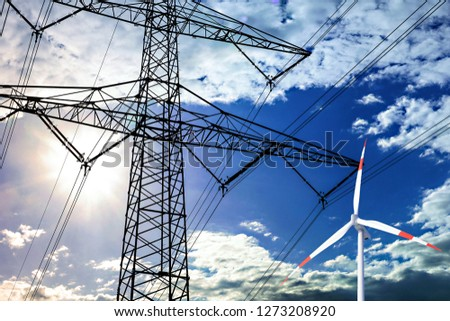 High voltage tower and wind turbine line in the sky. #1273208920