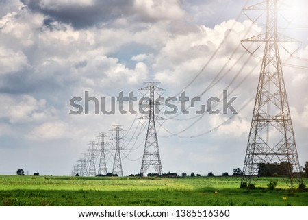 High voltage tower, Electric post and electric cable on the field in the countryside with white cloudy and blue sky background. Copy space Photo stock ©