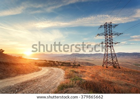 High voltage tower in mountains on the background of colorful sky at sunset.  Electricity pylon system. Summer evening. Industrial landscape