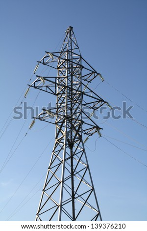High voltage tower on blue sky background.