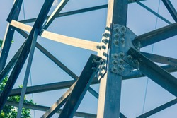 High-voltage tower support. Metal construction of the electric tower. Cross color processing.
