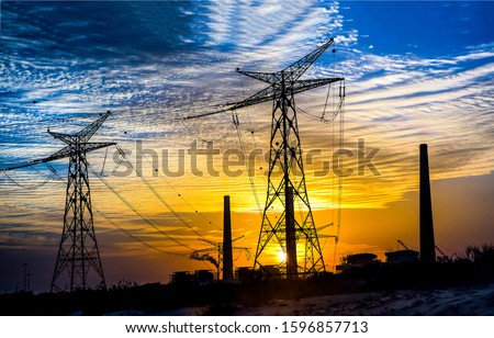 High voltage towers sunset silhouettes. Sunset high voltage towers on sky clouds. High voltage towers in evening sunset. Sunset high voltage towers