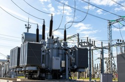 High voltage transformer against the blue sky. Electric current redistribution substation
