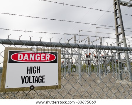 High-voltage transformer substation behind barbed-wire chain-link fence with Danger High Voltage sign.