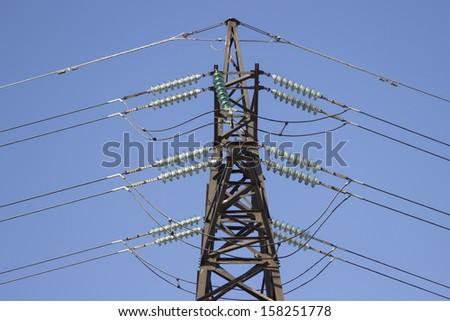 high voltage transmission pylon on blue sky background