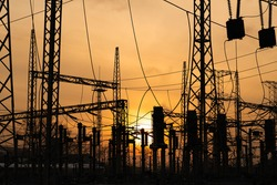 high-voltage wires against the background of a beautiful sunset sky. high voltage wires at dusk. Urban evening landscape. Silhouettes of power lines at sunset. Urban sunset. power plant at sunset