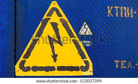 High voltage yellow sign mounted on blue metal rabitz grid with blue metal wall on background