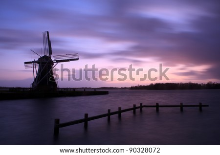 High water levels and a storm on the horizon at a Dutch windmill.