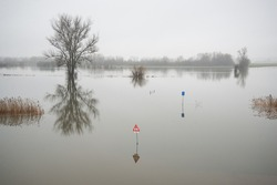 High water sign in a flooded river area Translation: