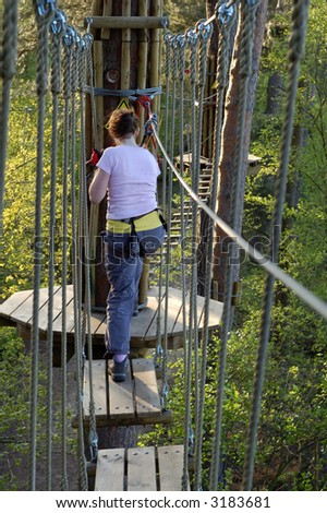 high wire forest adventure course of rope bridges, Swings and slides - stock photo