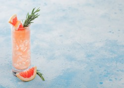 Highball glass of refreshing summer red grapefruit cocktail with ice cubes, fruit slice and rosemary on blue background. Space for text