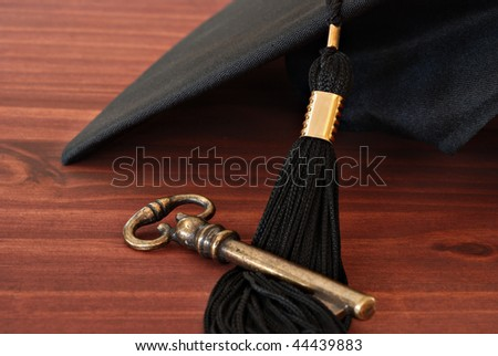 Higher education conceptual image of graduation cap and tassel with brass key on wood background.  Macro with extremely shallow dof.