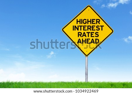 Higher interest rate road sign against empty field and blue sky