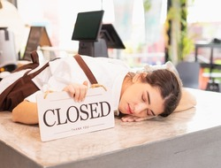 Higher right side angle of beautiful caucasian barista woman relax sleeping with show closed shop signs on coffee bar. Barista work at coffee bar and food service business