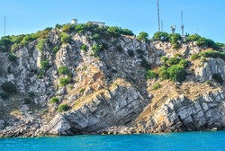 Higher rocks by blue sky. Summer landscape with stone cliffs, rocky sea shore